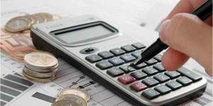 Uma mão segurando uma caneta, sobre a mesa moedas e uma calculadora