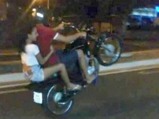 Dois jovens empinado moto