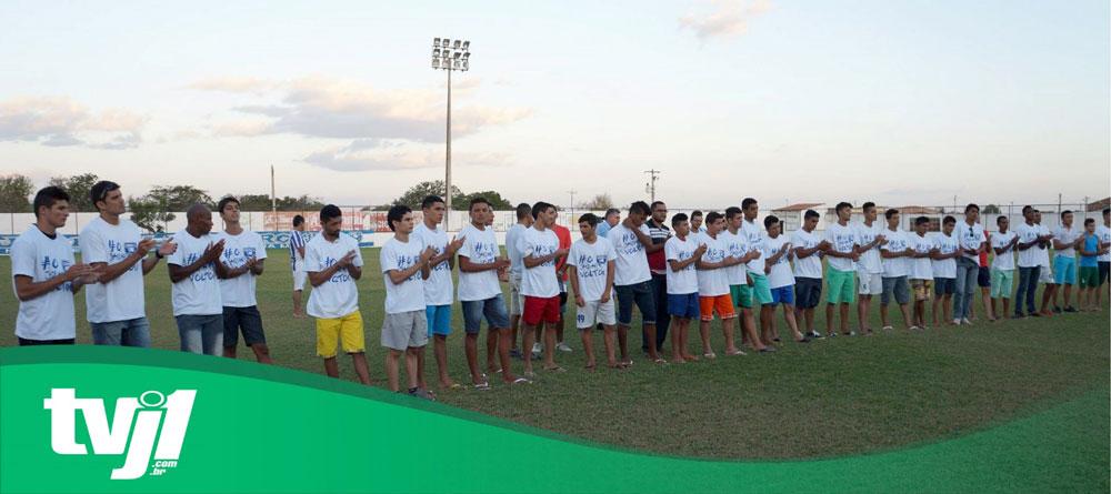 Jogadores batendo palmas, alinhados lado-a-lado no campo