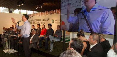 Camilo Santana falando ao microfone preso em pedestal, pessoas atrás e do seu lado esquerdo sentadas ouvindo.