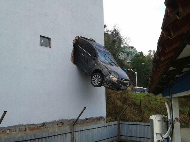 Carro preso em parede de um edifício.