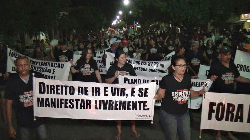 Pessoas vestindo preto segurando faixas em protesto