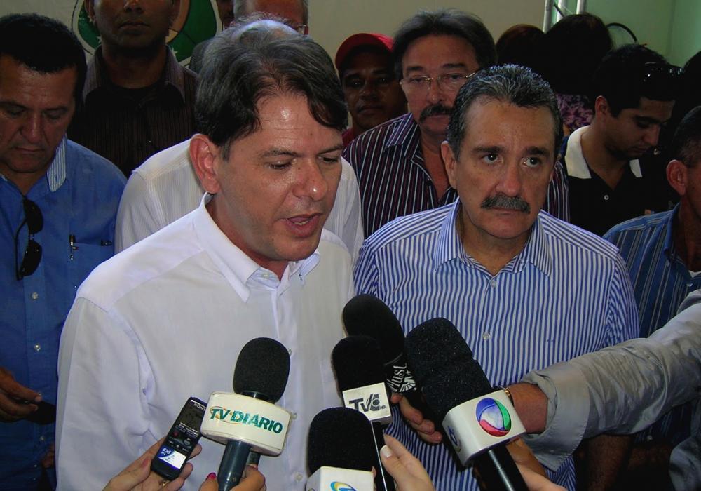 Cid Gomes dando entrevista para várias emissoras de TV e ao fundo vários homens