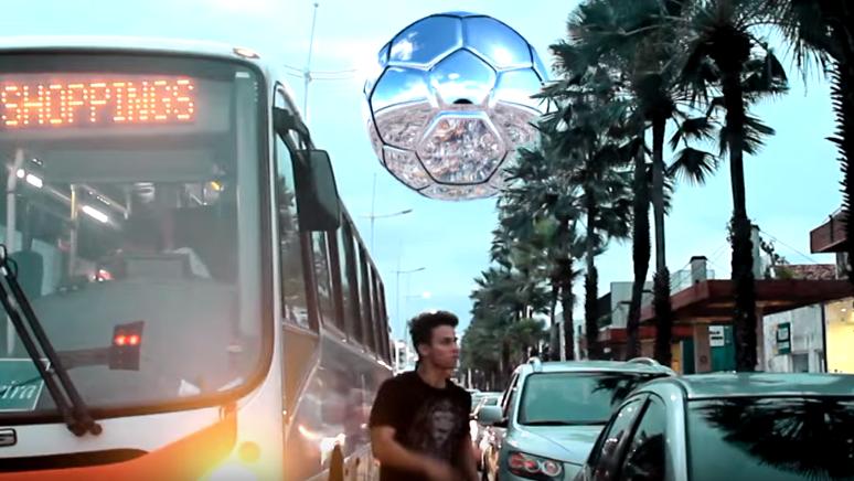 Pessoas correndo entre o trânsito e no céu ao fundo uma bola de futebol enorme.