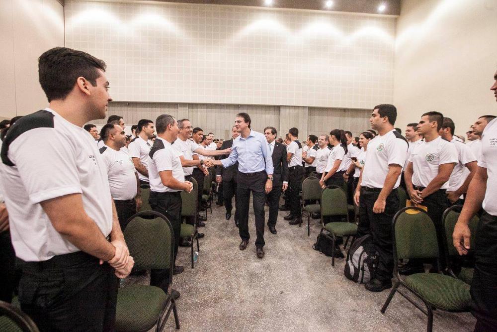 Pessoas em pé, trajando uniforme, cumprimentando o governador Camilo Santana