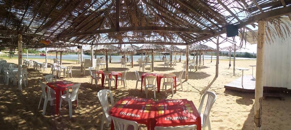 Cadeiras e mesas em areia, sob cobertas de palha e ao fundo águas de rio.