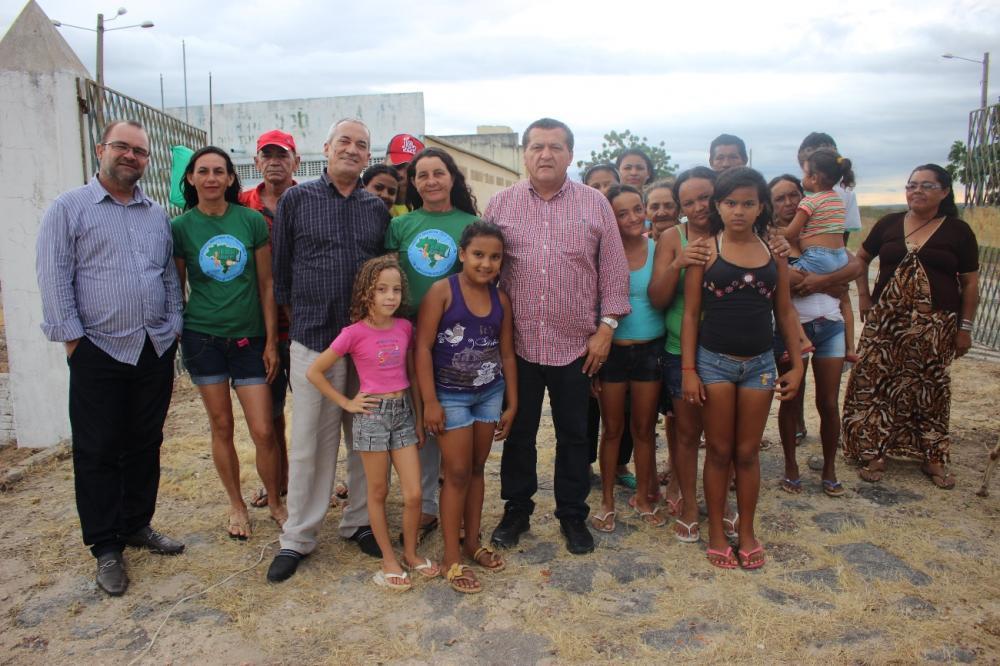 Homens, mulheres e crianças em pé, posando para foto.