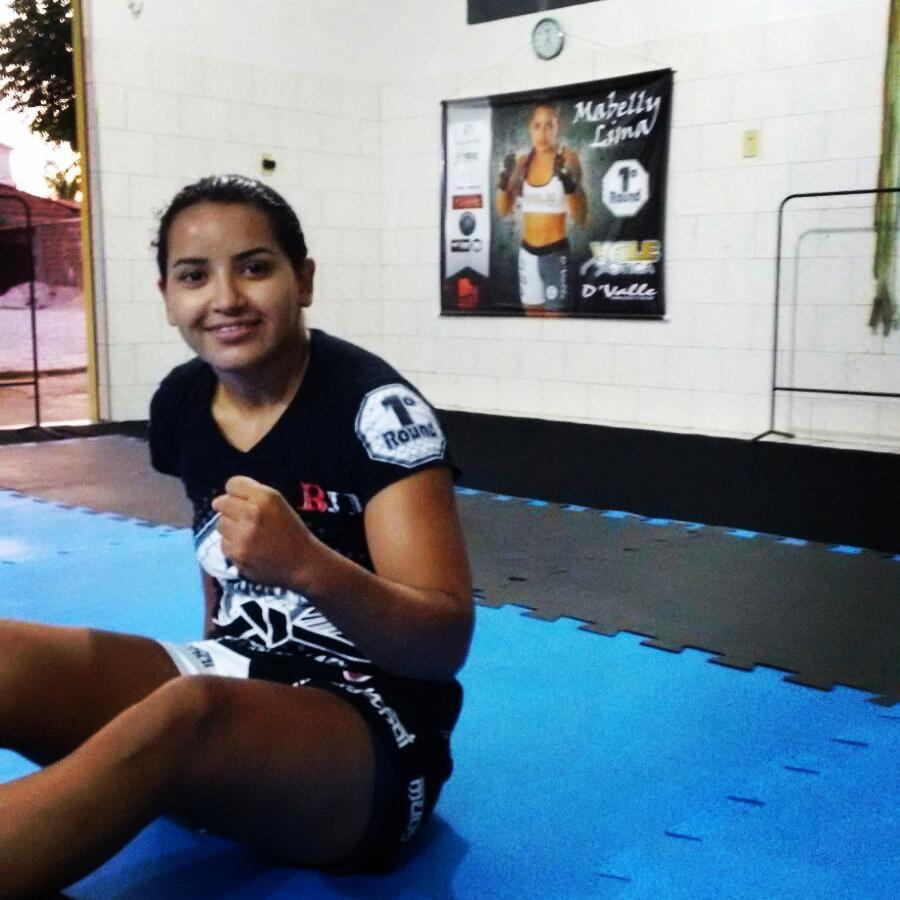 Mabelly Lima sentada em tatame