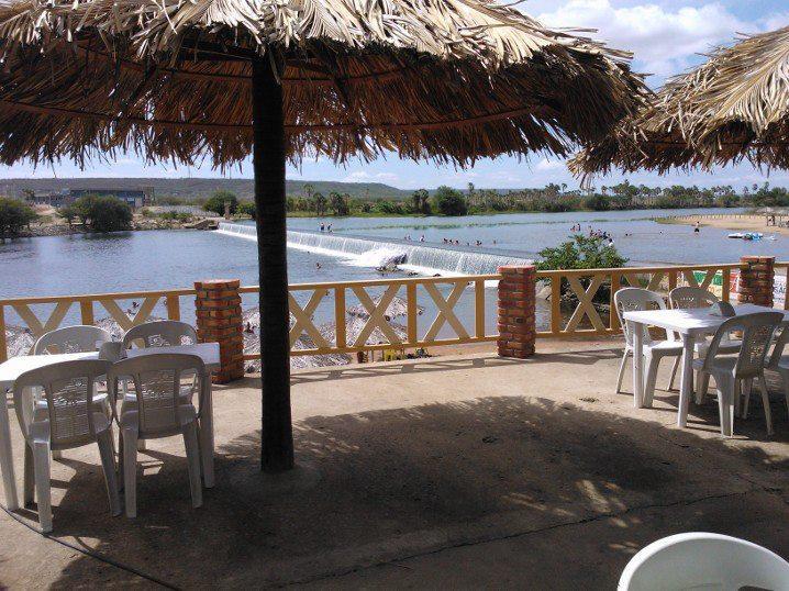Cadeiras e mesas sob coberta de palha em varanda com visão para barragem